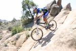 An Alpine Orthopedics rider takes the A-line on some granite slickrock.